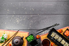 Sushi set sashimi and sushi rolls on dark background. Sushi set sashimi and sushi rolls served on plate with teapot, white flowers and tomatoes on dark wooden Stock Photo