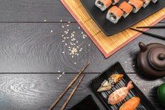Sushi set sashimi and sushi rolls served on dark background. Sushi set sashimi, nigiri, maguro and sushi rolls served on plate and teapot on dark wooden Stock Photo