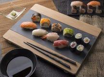 Sushi Set sashimi and sushi rolls served on stone slate stock images