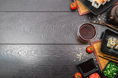 Sushi set sashimi and sushi rolls and tomatoes on dark background. Sushi set sashimi and sushi rolls served on plate with teapot and teabowl and tomatoes on dark royalty free stock photography