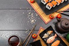 Sushi set sashimi and sushi rolls and tomatoes served on dark background. Sushi set sashimi, nigiri, maguro and sushi rolls served on plate and tomatoes with Stock Photos