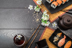 Sushi set sashimi and sushi rolls and white flowers on dark background. Sushi set sashimi, nigiri, maguro and sushi rolls served on plate and teapot with teabowl stock photography