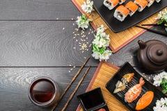 Sushi set sashimi and sushi rolls and white flowers on dark background. Sushi set sashimi, nigiri, maguro and sushi rolls served on plate and white flowers with Royalty Free Stock Photography