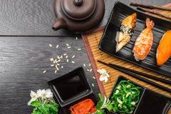 Sushi set sashimi and sushi rolls and white flowers on dark background. Sushi set sashimi, nigiri, maguro and sushi rolls served on plate with teapot and white stock image