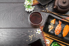 Sushi set sashimi and sushi rolls and white flowers on dark background. Sushi set sashimi, nigiri, maguro and sushi rolls served on plate with teapot and white royalty free stock image