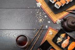 Sushi set sashimi and sushi rolls and white flowers on dark background. Sushi set sashimi, nigiri, maguro and sushi rolls served on plate with teapot and white Royalty Free Stock Photo