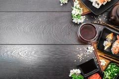 Sushi set sashimi and sushi rolls and white flowers on dark background. Sushi set sashimi, nigiri, maguro and sushi rolls served on plate with teapot and white Stock Photography