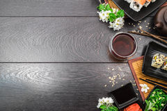 Sushi set sashimi and sushi rolls and white flowers on dark background. Sushi set sashimi and sushi rolls served on plate with teapot and teabowl and white Royalty Free Stock Images