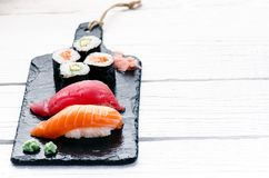 Sushi set served on a black slate. Sushi rolls and sashimi on a wooden white table. Seafood. Raw fish. White background. Wasabi. Sushi set served on a black Stock Photo
