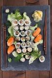 Sushi set on a slate stone. Sushi set on a slate board. Maki, uramaki and nigiri sushi stock image