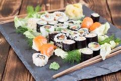 Sushi set on a slate stone. Sushi set on a slate board. Maki, uramaki and nigiri sushi stock images