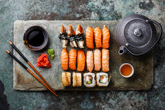 Sushi Set with tea on stone slate. Sushi Set with tea served on gray stone slate on metal background Stock Photos