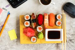 Sushi set on working place. Business lunch concept Stock Images