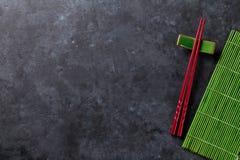 Sushi shopsticks op steenlijst stock foto