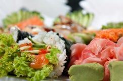 Sushi som är blandade med rulle, räcker rulle, sashimien, ingefära och Wasabi Royaltyfri Bild