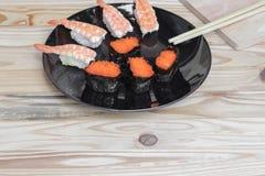 Sushi som är nära upp i svart platta på träbakgrund Royaltyfri Foto