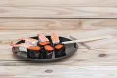 Sushi som är nära upp i svart platta på träbakgrund Royaltyfri Bild