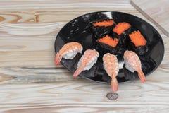 Sushi som är nära upp i svart platta på träbakgrund Arkivbilder
