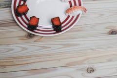 Sushi som är nära upp i svart platta på träbakgrund Arkivfoto