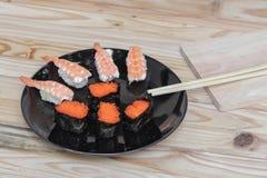 Sushi som är nära upp i svart platta på träbakgrund Royaltyfri Fotografi