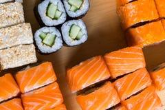 Sushi sortido e rolos na placa de madeira na luz escura Fotos de Stock Royalty Free