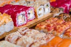 Sushi sortido e rolos na placa de madeira na luz escura Imagem de Stock Royalty Free
