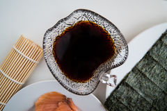 Sushi - Soy sauce in a bowl and ready for sushi. Soy sauce in a bowl with plates in the background ready for sushi Stock Images