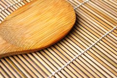 Sushi spoon. Over a bamboo wooden carpet Royalty Free Stock Photography