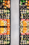 Sushi stellt Zusammenstellung in bento Kästen auf grauem Steinhintergrund, Draufsicht, vertikale Grenze ein Stockfotografie