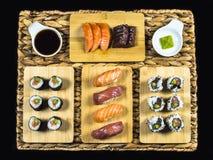 Sushi stellten auf Bambusplatte mit Sushi Rolls und Wasabi auf Weidenhintergrund ein Stockbild