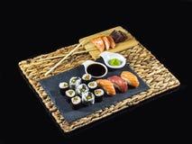 Sushi stellten auf Schiefer eine Bambusplatte mit Sushi Rolls und Wasabi auf schwarzem Hintergrund ein Lizenzfreies Stockfoto