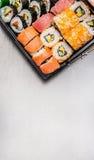 Sushi stellten mit Thunfisch nigiri ein, inner und Außenrollen im Transportkasten auf grauem Steinhintergrund, Draufsicht Stockbild