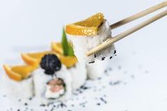 Sushi sui bastoni, isolati su profondità di campo bianca e bassa Immagine Stock