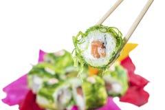 Sushi sui bastoni, isolati su profondità di campo bianca e bassa Fotografia Stock