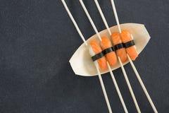 Sushi sul piatto a forma di della barca con i bastoncini Immagini Stock