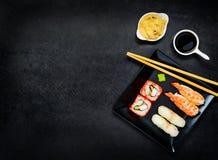 Sushi sul piatto scuro con lo spazio della copia Immagine Stock