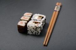 Sushi sulla tavola nera con i bastoncini Fotografia Stock