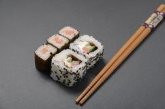 Sushi sulla tavola nera con i bastoncini Immagine Stock