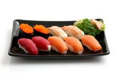 Sushi sur le paraboloïde noir d'isolement à l'arrière-plan blanc Photo libre de droits