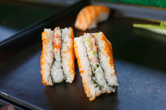 Sushi and sushi rolls. Served on black  tray at the market, various Stock Images