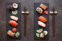 Sushi and sushi rolls, sushi nigiri on stone plate. On dark background stock images