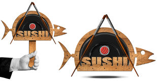 Sushi - Symbol with Wooden Fish. Two wooden symbols in the shape of fish with black plate, wooden and silver chopsticks, sushi roll and text Sushi. Isolated on Royalty Free Stock Photography