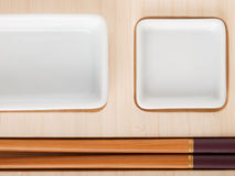 Sushi table with plates and sticks Royalty Free Stock Images