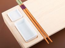 Sushi table with plates and sticks Royalty Free Stock Photos