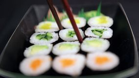 Sushi take away box. Eating maki sushi roll with chopsticks from take away box. Delicious sushi eating stock footage