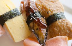 Sushi. Tamago egg custard, unagi broiled eel, and inari bean curd skin sushi pieces on rice wrapped with a band of seaweed royalty free stock photos