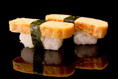Sushi tamago nigiri. Isolated on black royalty free stock photo