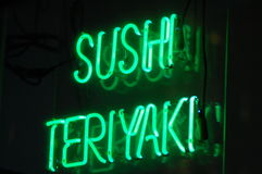 Sushi Teriyaki Neon. A neon sign in a restaurant window advertises sushi and teriyaki for sale within Stock Image