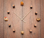 Sushi time. In the form of a wall clock on a wooden background Royalty Free Stock Photography