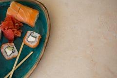 Sushi in turkooise ceramische plaat op marmeren tafelblad Stock Foto's